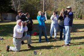 Participants getting shots of Jerri the Screech Owl held by fellow participant, Jim