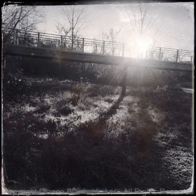 The sun rises from behind a bridge, casting long shadows over frost. Hipstamatic app, D-Type film, iPhone 5S.